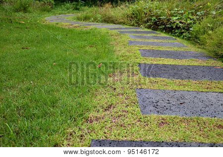 Pathway Of Stone Bricks In A Grass Field