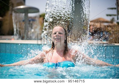 Young Woman Relaxing Under Swimming Pool Fountain