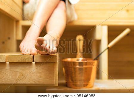 Woman Relaxing In Sauna. Female Feet.