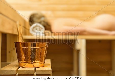 Spa Accessories In Sauna. Woman On Background.
