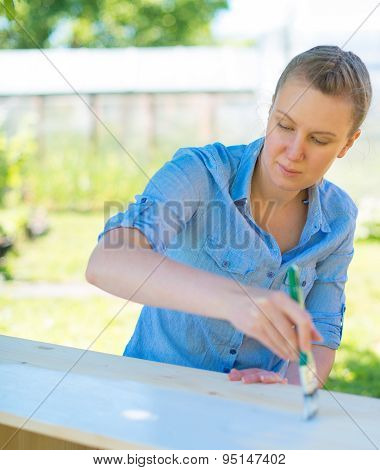 Woman With Brush Painting Wooden Furniture.