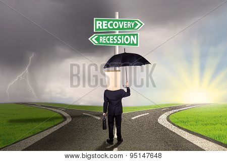 Businessperson With Signboard To Recovery Or Recession Financial
