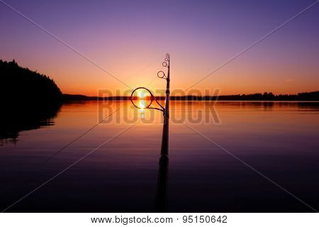 Sunset on a summer lake seen through a fishing rod ring