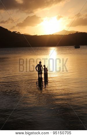 Antigua, West Indies- March 20, 2014: Family Fishing At Sunset