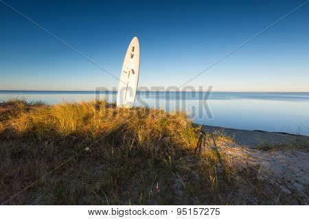 Surfing Board Pounded In Sand On Sea Shore