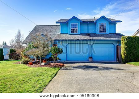 Large Bright Blue House With Two Grarage Doors.