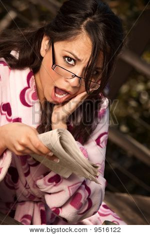 Pretty Hispanic Woman In Bathrobe With Newspaper