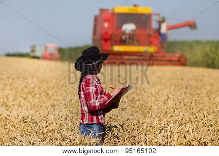 Young Woman In Wheat Field During Harvest