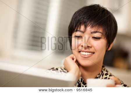 Pretty Smiling Multiethnic Woman Using Laptop