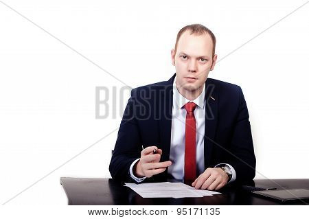Businessman in red tie at the table gives a pen to sign  contract