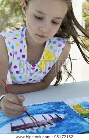Portrait Of A Young Girl Drawing A Picture Outdoors