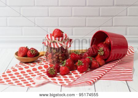 Ripe strawberry in jar and red pot