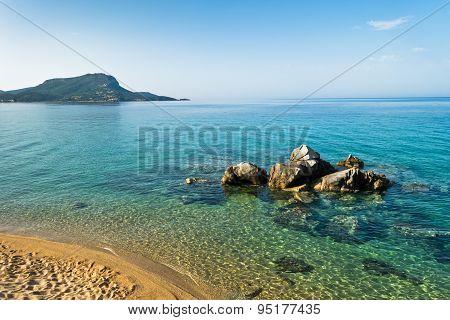 Sea rocks near sandy beach at early morning
