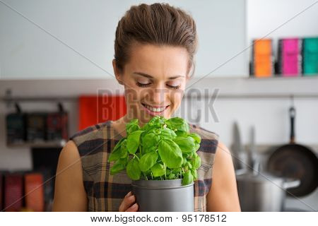 Smiling Woman Holding And Smelling Pot Of Fresh Basil