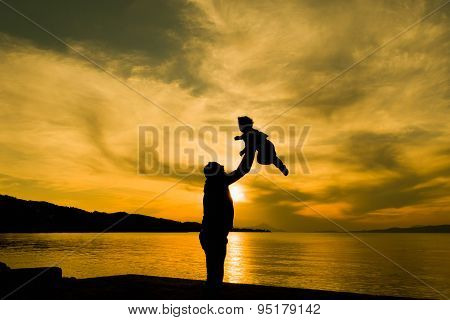 Family loving moment with father and son against dramatic sky.