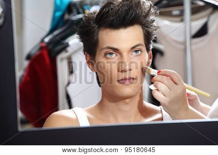makeup artist applying foundation with a brush man in the dressing room mirror