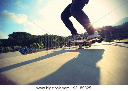 skateboarder legs doing a trick ollie at skatepark