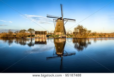 Windmill Reflecting In Water In Netherlands