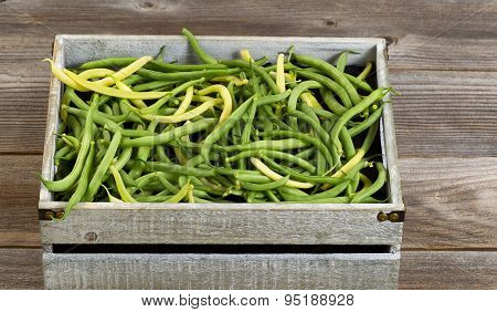 Green And Yellow Beans In Old Crate On Rustic Wooden Boards