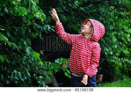 happy child girl in red raincoat playing under the rain in summer garden