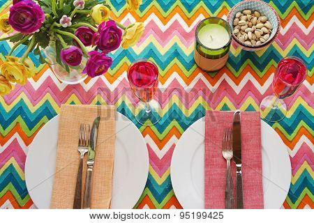 Overhead Bright Colorful Table Setting With Chevron Tablecoth