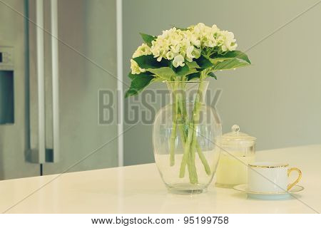 Glass Vase Of White Flowers And Teacup In A Kitchen With Blurred Fridge Behind In Soft Green Hues