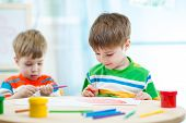 foto of day care center  - smiling children draw and paint at home or day care center - JPG
