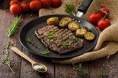 image of ribs  - Beef rib eye steak with rustic potatoes fresh herbs and tomatoes sprinkled sea salt and herbs - JPG