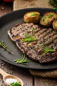 picture of ribs  - Beef rib eye steak with rustic potatoes fresh herbs and tomatoes sprinkled sea salt and herbs - JPG
