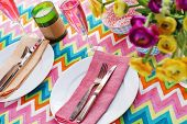 image of champagne color  - Bright colorful table setting with multi colored chevron pattern tablecoth - JPG