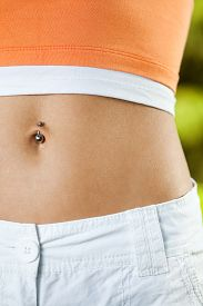 stock photo of pierced belly button  - Close up image of perfectly shaped female stomack - JPG