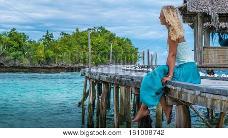 Girl Sitting on Wooden Pier of an Homestay looking into blue ocean, Bamboo Hut in background, Gam Island, West Papuan, Raja Ampat. Indonesia