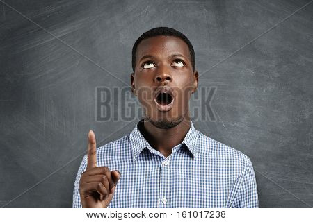 Portrait Of Surprised African Employee In Checkered Shirt Pointing His Index Finger Above His Head,