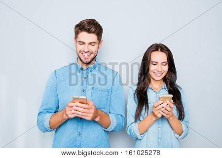 Happy Young Couple In Love Typing Sms On Smartphones