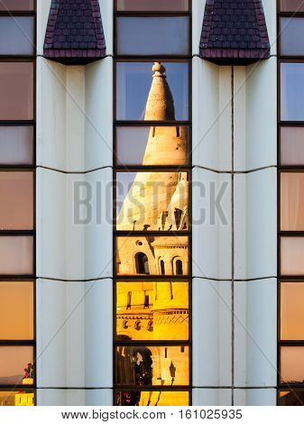 Detailed view of warped reflection of Fisherman's Bastion, aka Halaszbastya, fairy tale towers in windows of modern hotel. Architectural constrast of historical landmark and hated modern architecture of communistic Hungary. Budapest, capital city of Hunga