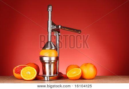 Exprimidor y naranjas sobre fondo rojo