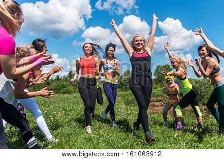 Group of women running outdoors having fun in nature.