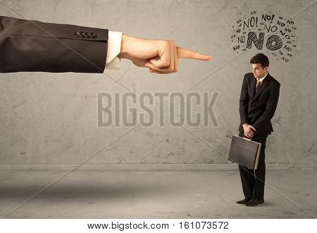 A young employee disagreeing and arguing with boss, feeling ashamed concept. A large hand pointing at businessman saying no