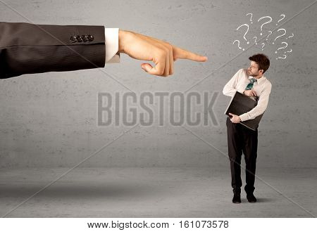 Young amateur confused businessman not understanding why he is getting fired concept with drawn question marks and large boss hand pointing at him