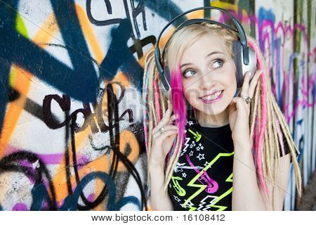 portrait of young woman with headphones at graffiti wall