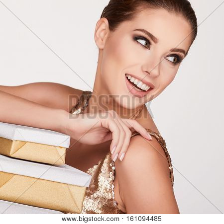 Portrait of a happy woman opening gift box and looking at camera over gray background