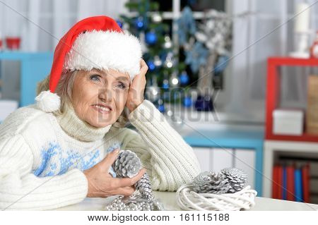 Portrait of smiling senior woman with Christmas decorations sitting at the table at home