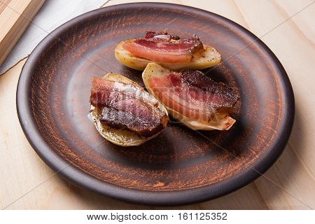Baked Potatoes With Slices Of Bacon On Wooden Background.