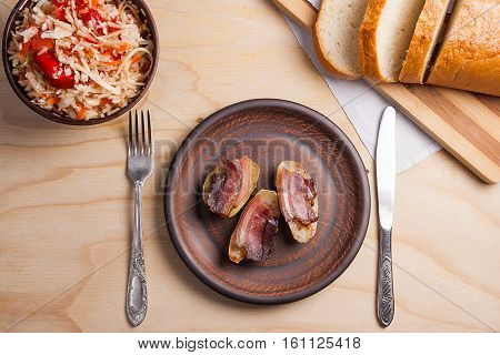 Baked Potatoes With Slices Of Bacon And Eating Utensils On Wooden Background. Sauerkraut In Clay Bow