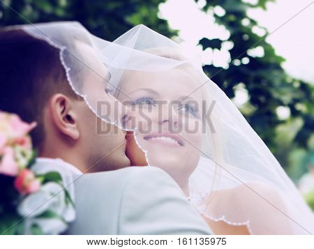 Moscow, Russia - June 22, 2015: Bride embraces bridegroom shines with happiness.