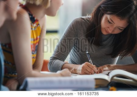 Young woman taking notes from books for her study. Students sitting at table with books preparing school assignment.