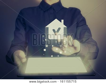 Image of a girl with tablet in her hands. She looking for a house for buying or for rent using online searching service.Real estate. Online for buying or for rent.