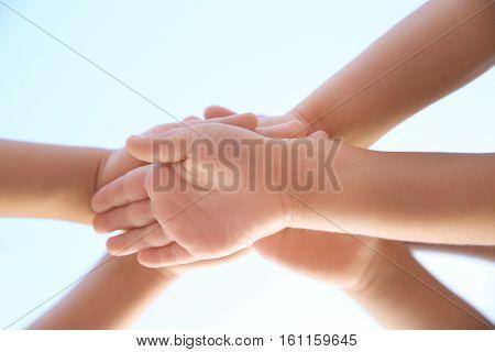 Children hands against blue sky