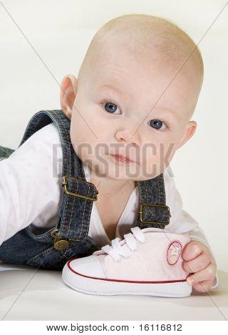 Porträt von lying down Baby Girl holding einen Schuh