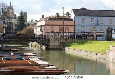 CAMBRIDGE, UK - FEBRUARY 10 2016: Pedestrians walk along Bridge Street, Cambridge, England on a sunny winter day, passing a row of punts on the River Cam, college buildings, shops and a pub.